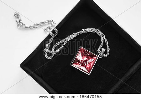 Large red gem pendant on silver chain in jewel box closeup