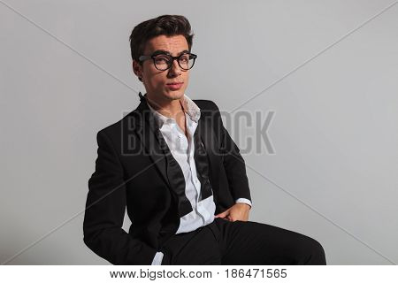elegant man with undone bowtie and glasses sitting and looking at the camera on grey background