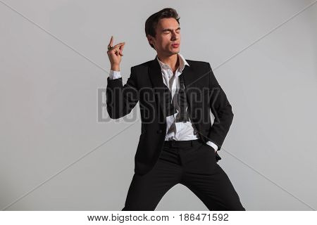 elegant man in tuxedo snapping his fingers and blinks on grey background