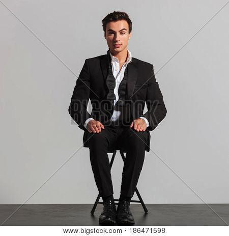 elegant man in suit and undone bowtie sitting on chair on grey studio background