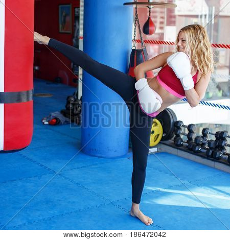 Young sporty woman kicking into heavy bag in gym