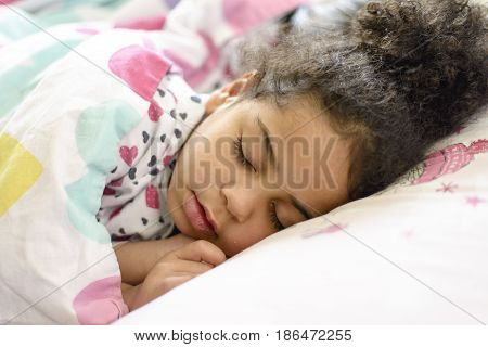 Little African American girl resting in bed
