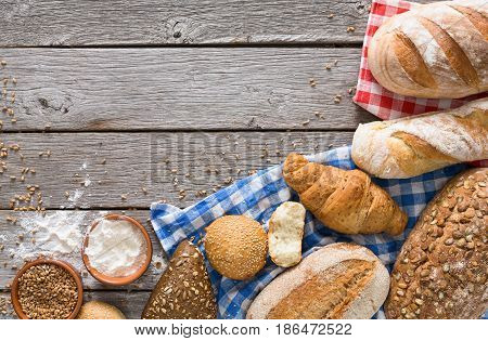Fresh white bread background, top view with copy space. Homemade baguette loaves on rustic wood