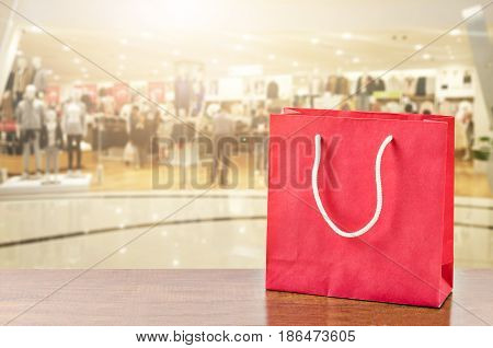 Red shopping bag on wooden table over blurred mall background.