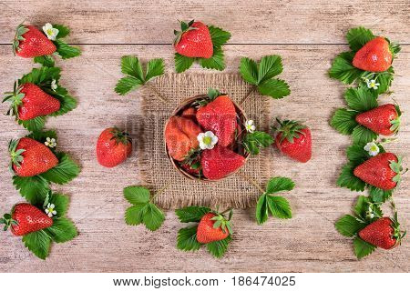 Decorative arrangement of fresh strawberries with leaves on vintage background