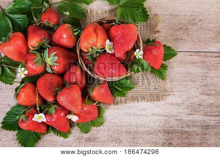 Basket of fresh strawberries with leaves on vintage background. Top view of ripe strawberry fruits
