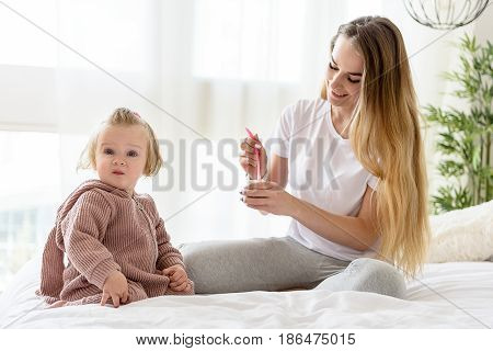 Pretty baby is eating food fusion and looking at camera with surprise. Her mother is holding jar with spoon and smiling