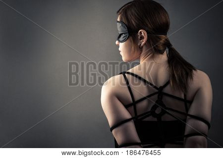 beautiful woman in mask and bondage isolated on gray background