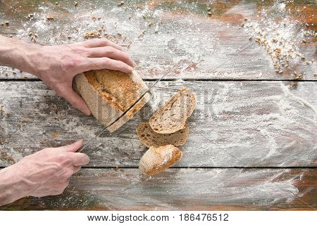 Baking background. Hands of baker cutting bread loaf with knife on rustic wooden table sprinkled with flour.