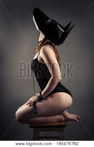 sexy woman in dog mask sitting kneeling on chair and looking up