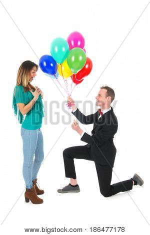 Man is doing a proposition de mariage with balloons and ring
