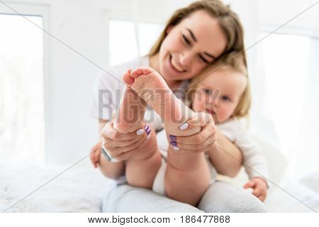 Happy mother is holding small legs of her infant and looking at it with admiration. She is sitting on bed and smiling. Focus on feet of the girl