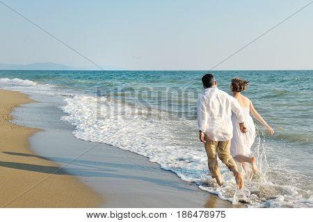 Happy couple walking on the beach near sea holding hands