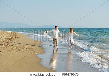 Happy couple running on the beach near sea