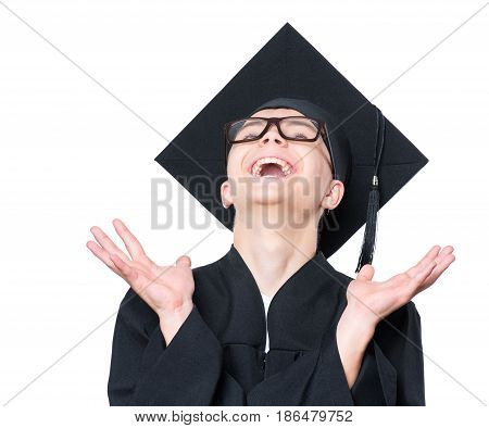 Portrait of a surprised graduate teen boy student in a black graduation gown, hat and eyeglasses, looking up with wide open mouth - isolated on white background. Educational concept.