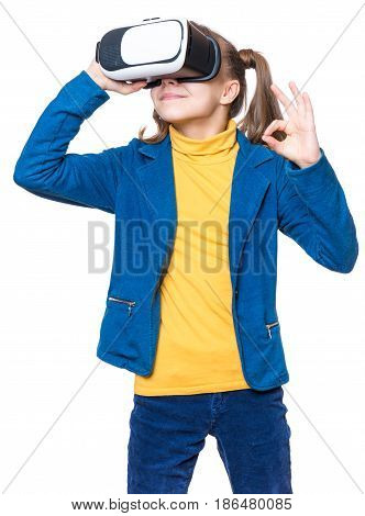 Happy little girl wearing virtual reality goggles watching movies or playing video games, isolated on white background. Cheerful smiling kid looking in VR glasses and making ok gesture.