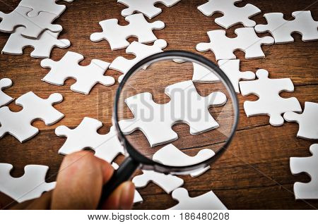 Hand with magnifying glass on white jigsaw puzzle on wooden background.