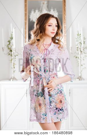 Gorgeous and beautiful girl seductive posing, holding strap of floral printed dress in hand.Pretty woman with wavy hair and perfect make up after beauty salon posing in luxury interior against mirror.