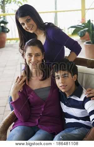 Mother, son and daughter sitting on porch
