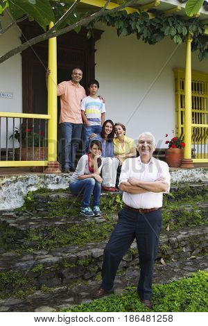 Hispanic family on house steps together