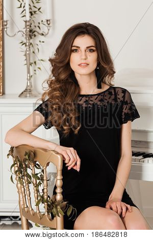 Seductive pretty brunette girl female sitting on chair with element of gold and posing at camera in black nightie. Woman with wavy hairstyle and perfect make up leaning on chair. Luxury interior.