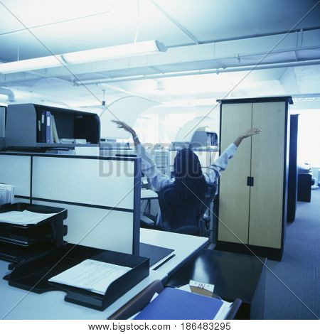 African American businesswoman stretching in office cubicle