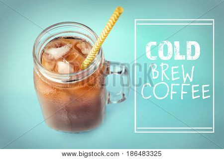 Glass jar of cold brewed coffee with milk on color background