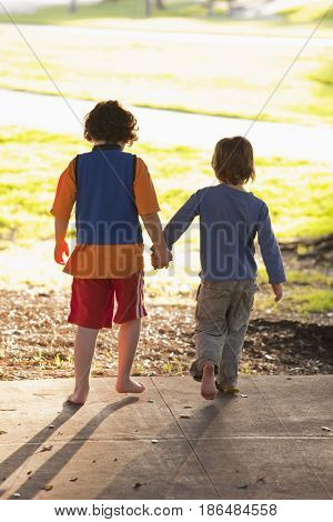 Caucasian brothers holding hands