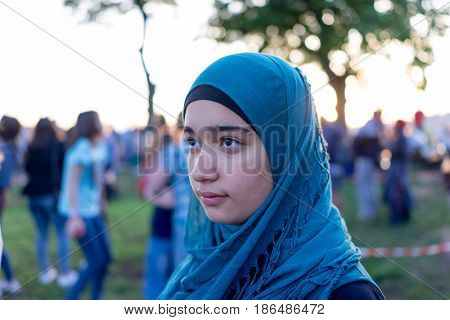 happy muslim girl with people in background