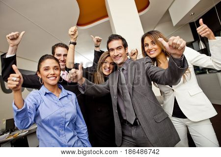 Hispanic business people giving the thumbs up