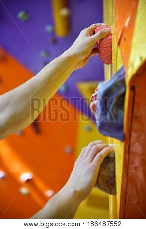 Climber On Artificial Climbing Wall In Bouldering Gym Without Insurance. Close Up