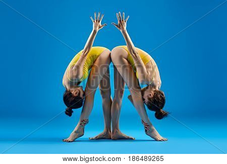 Two Young Women Doing Yoga Asana Standing Parsvottanasana