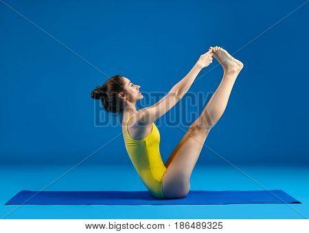 Young woman doing yoga asana both big toes pose. Ubhaya Padangusthasana