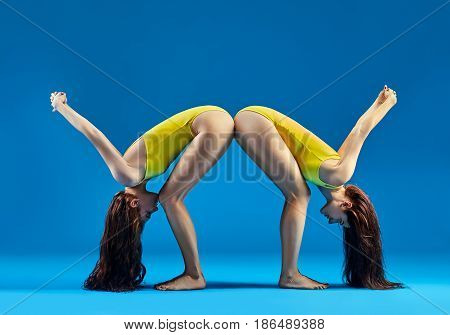 Two Women Doing Yoga Asana Standing Forward Bend Pose Variation