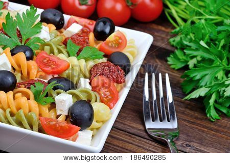 Pasta with vegetable in a plate and fork on table