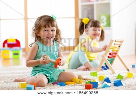 Little kids preschoolers playing with abacus and constructor toys on floor in kindergarten or home. Early learning concepts.