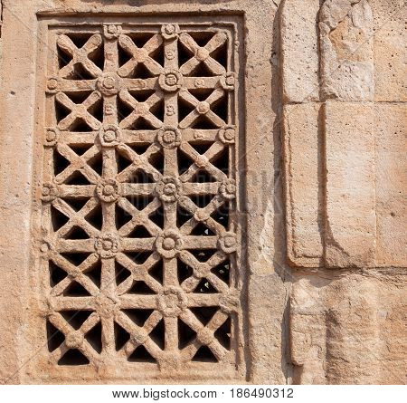 Design of carved window on Indian rock-cut architecture example. 7th century Hindu temple in town Pattadakal, India.