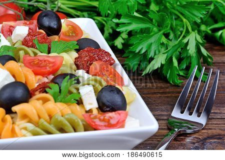 Colorful pasta with vegetable and fork on wooden table