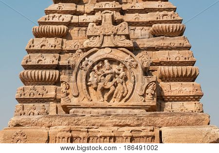 Dancing Hindu gods on roof of temple India. Example of Indian architecture in Pattadakal, UNESCO World Heritage site with stone carved structures of 7th and 8th-century