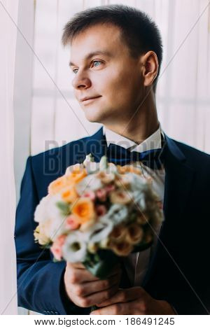 Ellegant dressed romantic groom holding a wedding bouquet of white and pale orange roses in hands standing near the window.