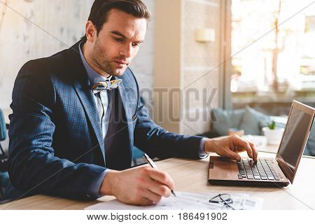 Restrained bristled male making notes while working at laptop comfortable in office