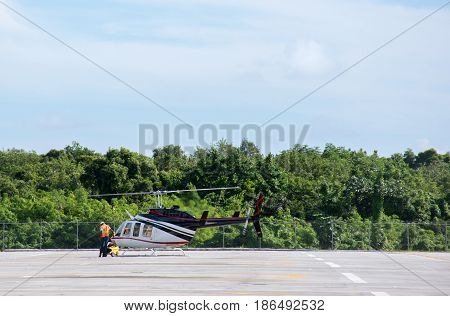 The Helicopter Is Being Prepared For Take-off, Stands On A Helipad With A Blue Sky