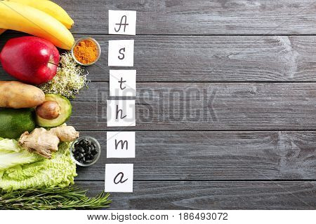 Text ASTHMA and set of healthy products on wooden background