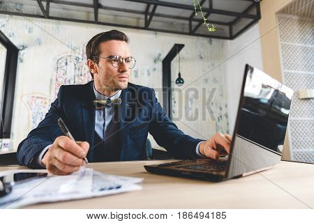 Serious bristled businessman making notes by pen while working with laptop in comfortable office