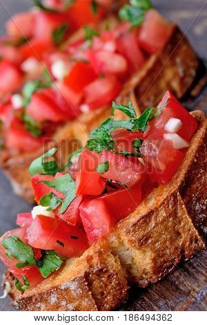 Bruschetta with tomatoes garlic and parsley on wooden table