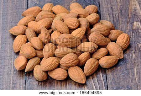 Group of almonds on wooden table closeup