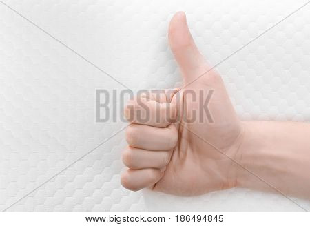 Male hand showing thumb up sign and orthopedic pillow on background. Healthy posture concept