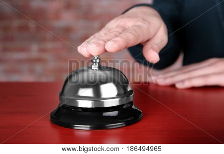 Woman ringing service bell in hotel lobby