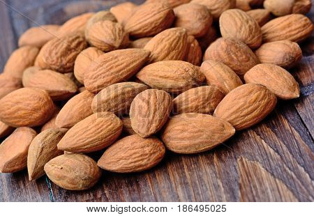 Heap of almonds on wooden table c