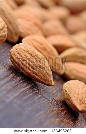 Heap of almonds on wooden table closeup
